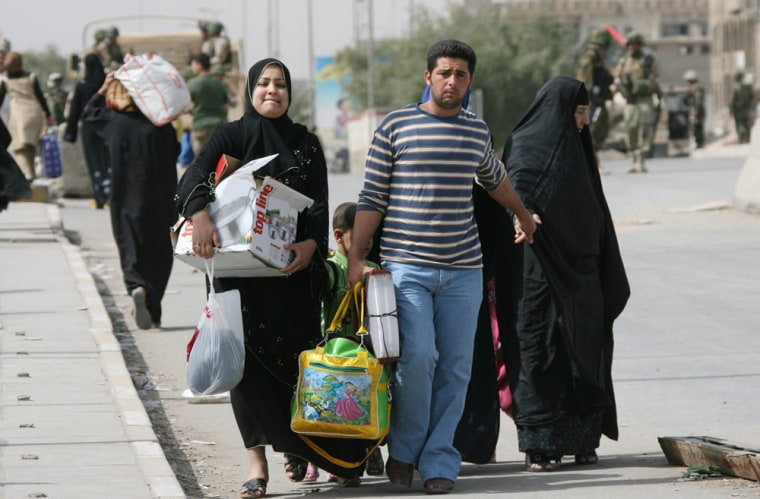 Image: An Iraqi family leaves the Shiite enclave of Sadr City Baghdad.