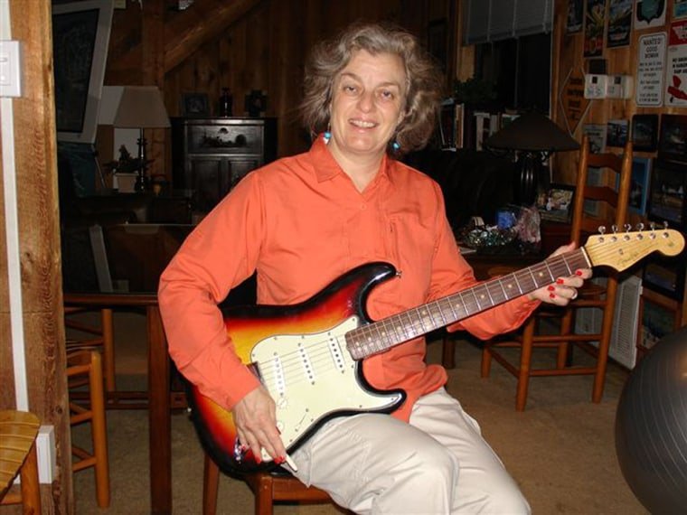 Image: Martin Whatley holding her husband's 1964 Fender Stratocaster guitar