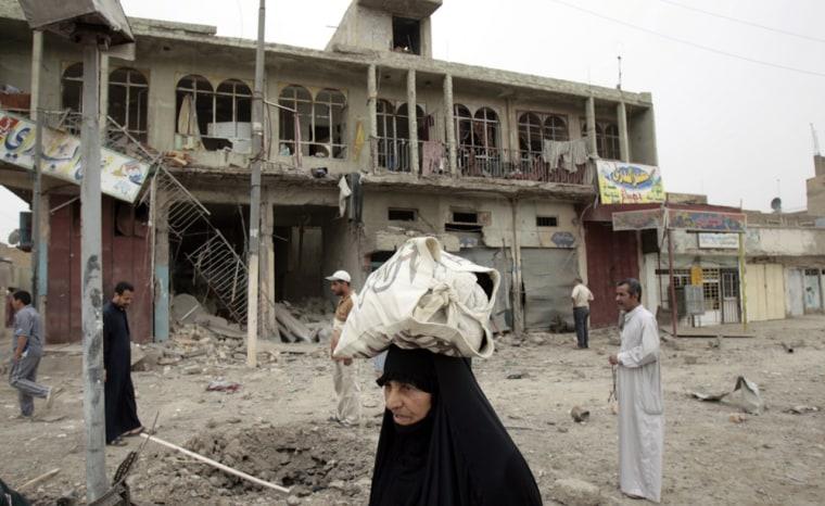 Image: An Iraqi woman walks past a building badly damaged.