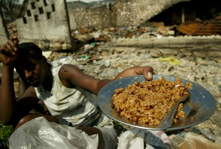 Image: A Haitian woman shows a dish with rice, main ingredient of the Haitian diet,