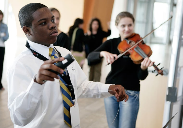 David Price from Verbum Dei High School tries his hand at conducting an on-screen orchestra at the UBS Virtual Maestro exhibit, during a tour stop in Los Angeles last November.