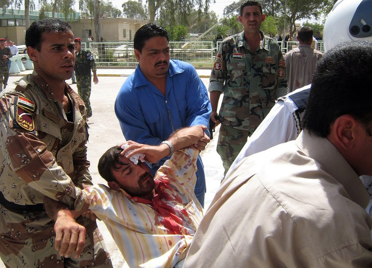 Image: Iraqi soldiers and hospital employees carry an injured man in Baquba.
