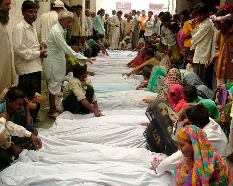 Image: Relatives sit next to the bodies of victims.