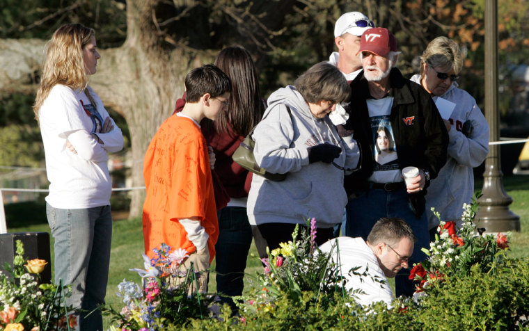 Image: Mourners place flowers on the memorial stones.