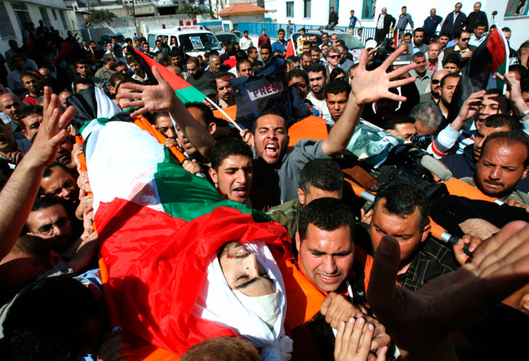 Image: Palestinian mourners carry the body of Reuters cameraman Shana during his funeral in Gaza City