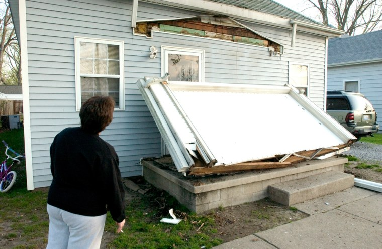 Image: Janet Clem, 37, looks at the damage to her home in Mt. Carmel, Ill