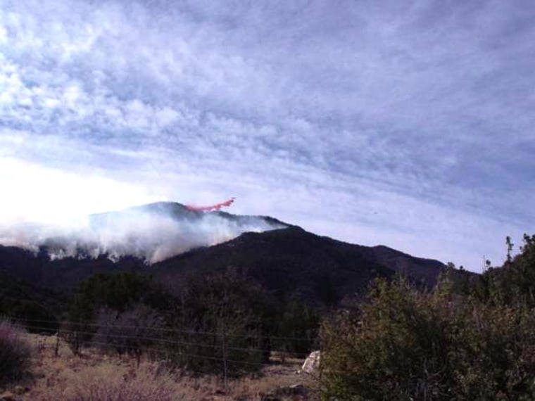 An airtanker dumps a load of fire retardant on top of the fire burning near Manzano, N.M.