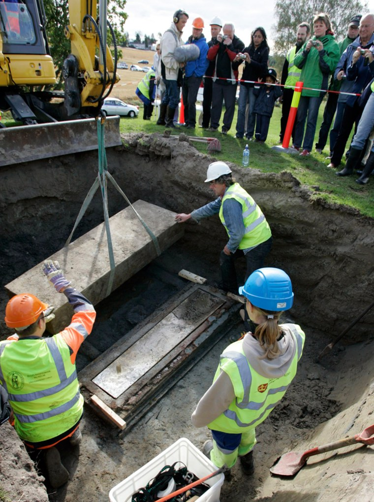 Image: Archaeologists exhume a body