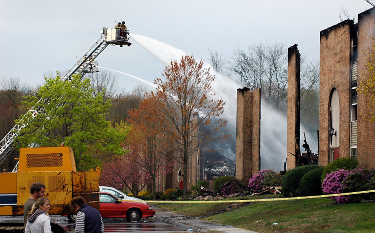 Image: Firefighters cool down the fire which destroyed the Peachtree Garden Apartments complex in Norwich, Conn.
