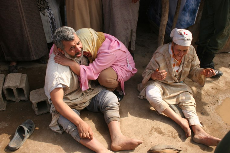 Image: Victims' relatives cry on the site of a fire that broke out in a mattress factory in Casablanca, Morocco