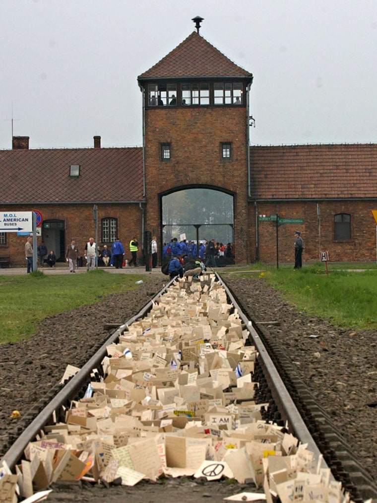 Image: People place memory plaques on rails in Birkenau