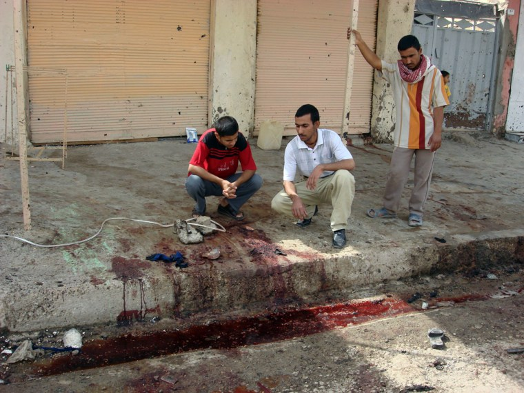 Image: Iraqis look at the site of a suicide bombing in Balad Ruz, Iraq.