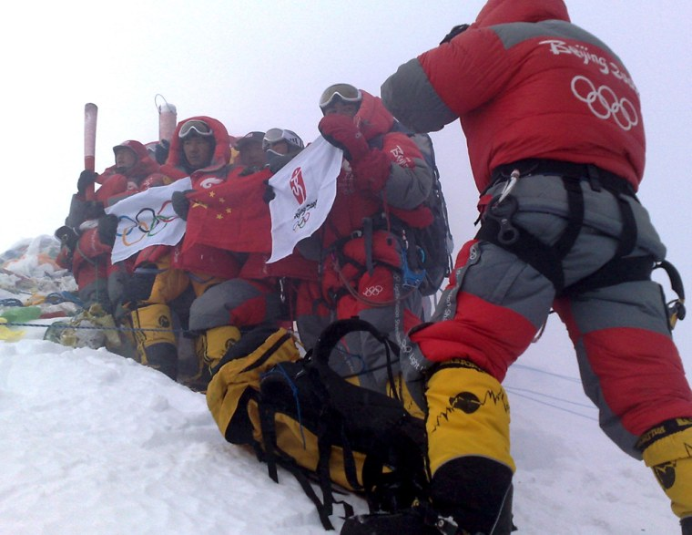 Image: Chinese climbers cheer with the Olympic torch and flags at the top of the Mount Everest