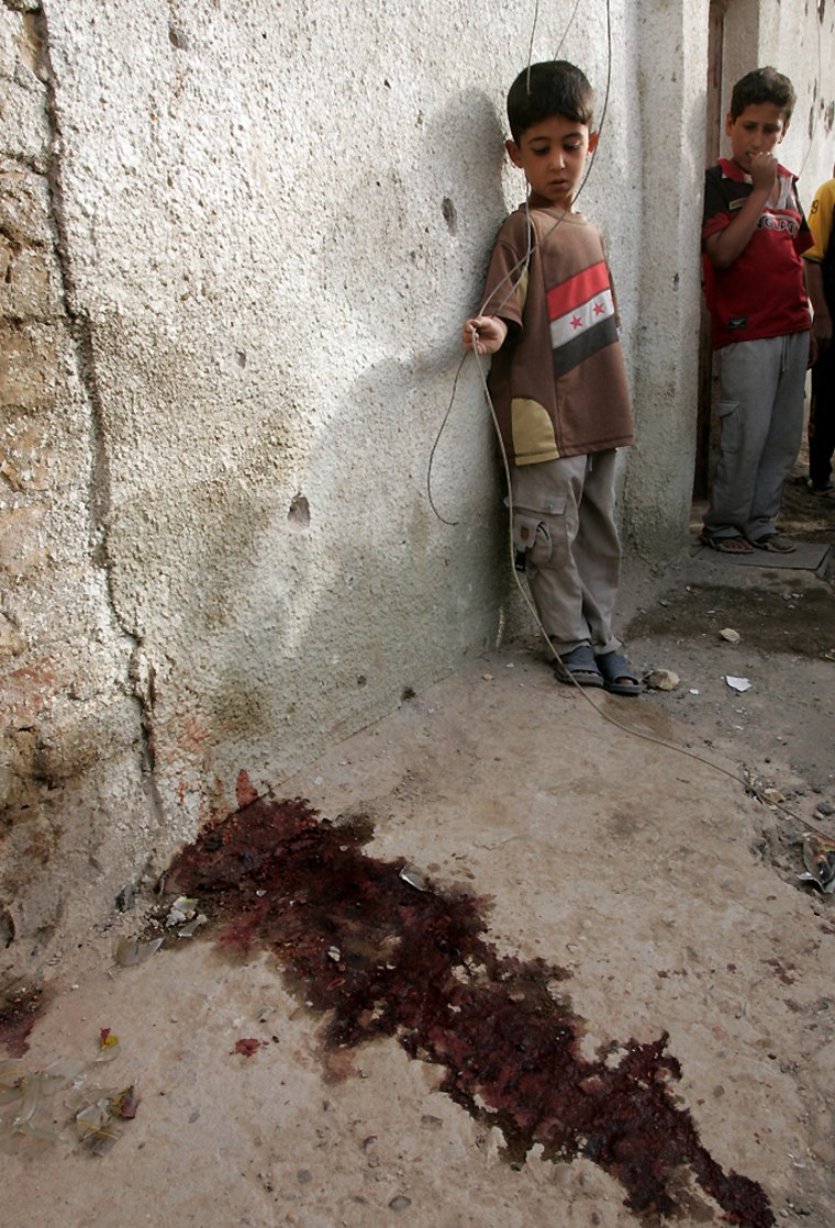Boys look at blood stains on the ground after clashes in Baghdad's Sadr City