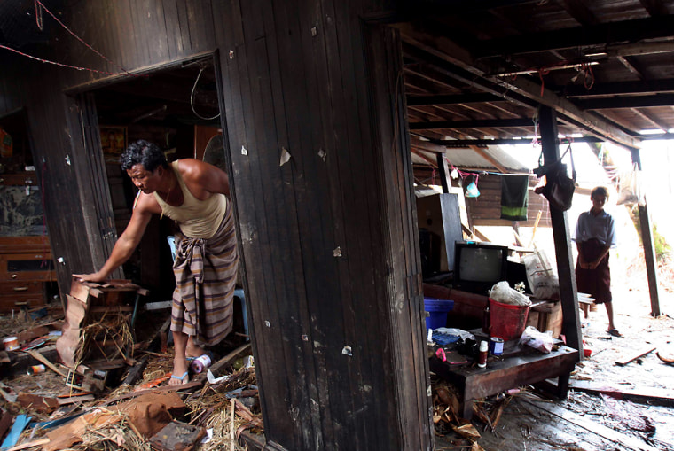 Image: Myanmar man surveys the damage to his house at Mangalay village