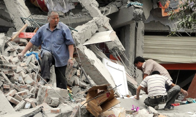 Image: Rescuers search the rubble of the collapsed Juyuan middle school
