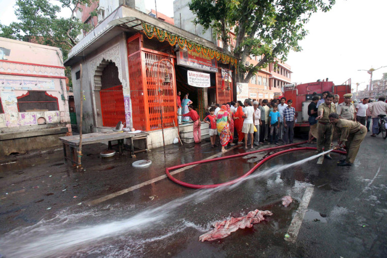 Image: An Indian firefighter washes off one of the blast sites in Jaipur, India