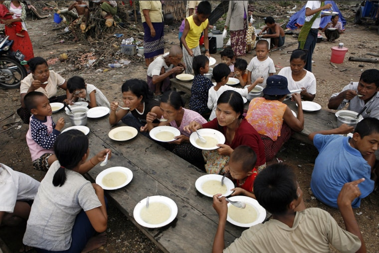 Image: Internally displaced people eat at a relief centre near Dedaye, Myanmar