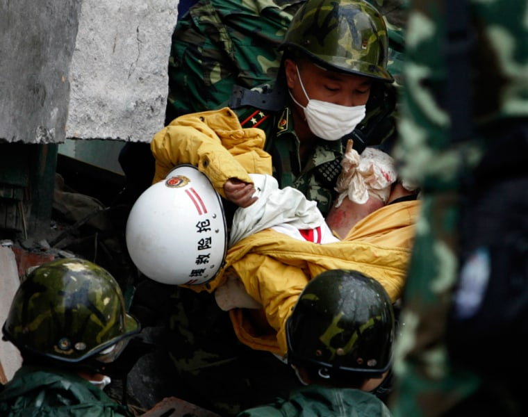 Image: Rescuer carries high-school student Yang Liu from rubble in Hanwang
