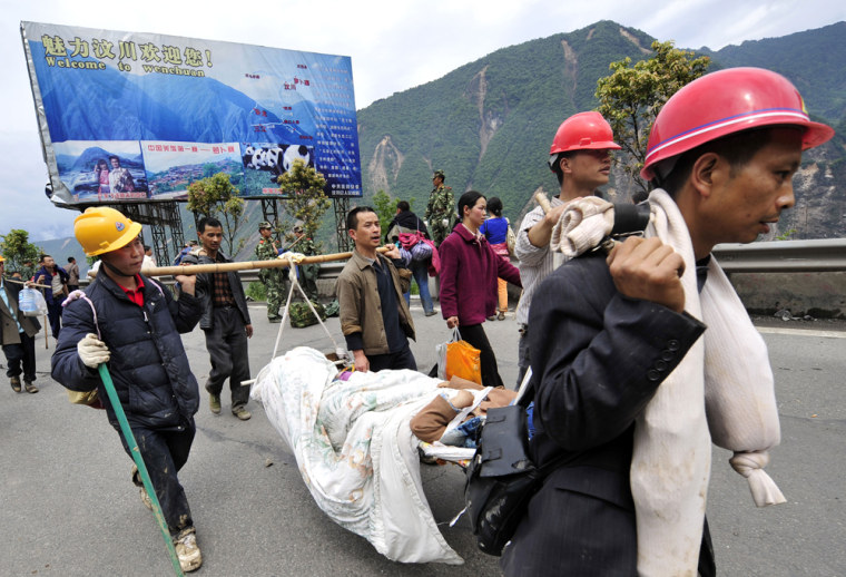 Image: Survivors carry an injured man
