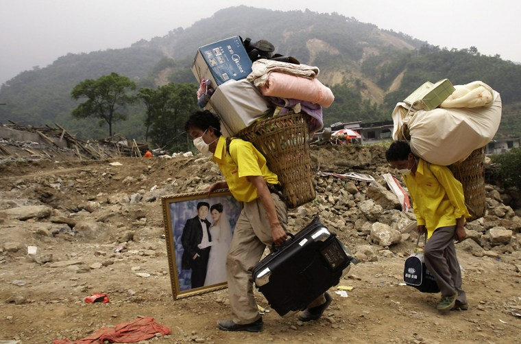 Two residents, one carrying a wedding picture of relatives and and other belongings, leave the disaster area in Beichuan county on Saturday. The man in the wedding image was killed in Monday's earthquake.