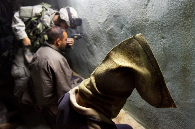 An Iraqi detainee sits with his head covered by a sand bag while an American soldier covers another detainee's eyes with tape during a raid in Ramadi on Feb. 4, 2006.