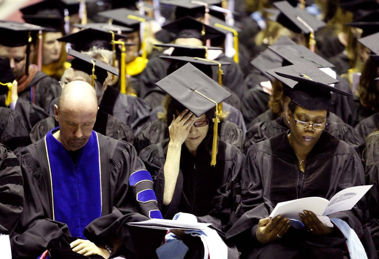 Image: Members of the graduating class of 2008 at Northern Illinois University bow their heads during a moment of silence for those slain during the Feb. 14, 2008 shootings on campus