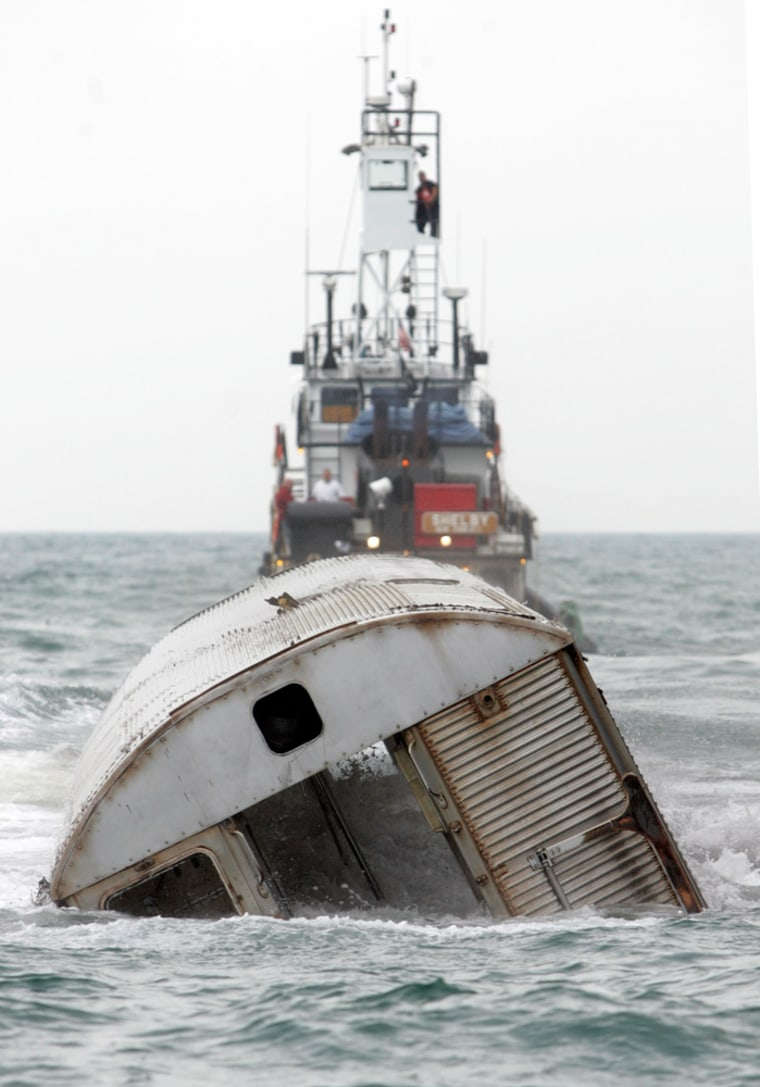 Image: A retired New York City subway carriage is dropped into the Atlantic Ocean to create an artificial reef near the coast Of Ocean City