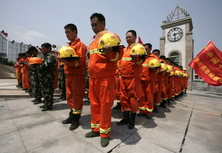 Rescuers pay tribute to those who died in earthquake, in front of a clock which stopped the minute the earthquake hit, in the township of Hanwang