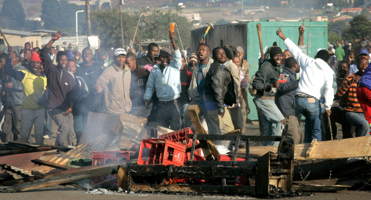 Image: South Africans holding sticks and knifes shout