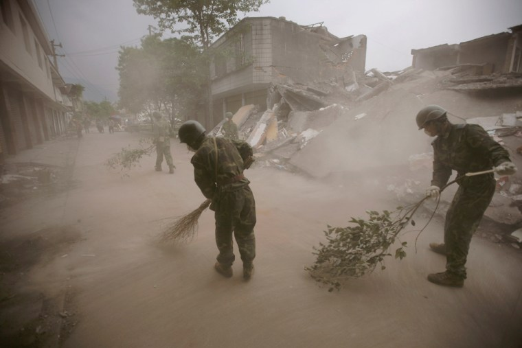 Soldiers clean broken glass from a roadin Hanwang town Wednesday next tobuildings destroyed by lastweek's earthquake in China.