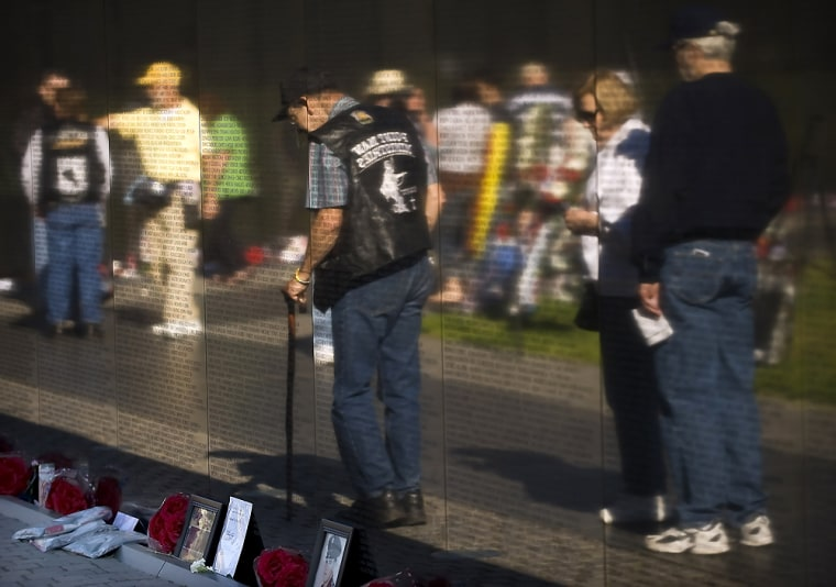 Image: Visitors file by the Wall, which currently contains 58,249 names of fallen soldiers