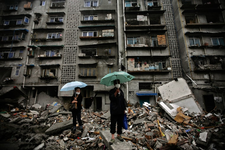 Image: Chinese watch from the ruins of collapsed buildings, as workers clean the street