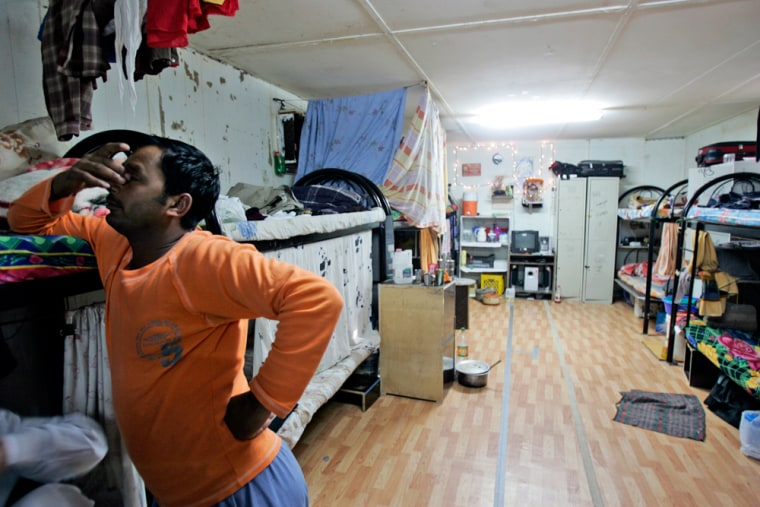 An Indian laborer rubs his eyes as he stands next to his bed at a labor camp in Dubai, United Arab Emirates, Feb. 22, 2008. Dubai's astonishing building boom, which has made it one of the world's fastest-growing cities, has been fueled by the labor of about 700,000 immigrants, almost all from poor, rural villages in India, Pakistan and Sri Lanka.