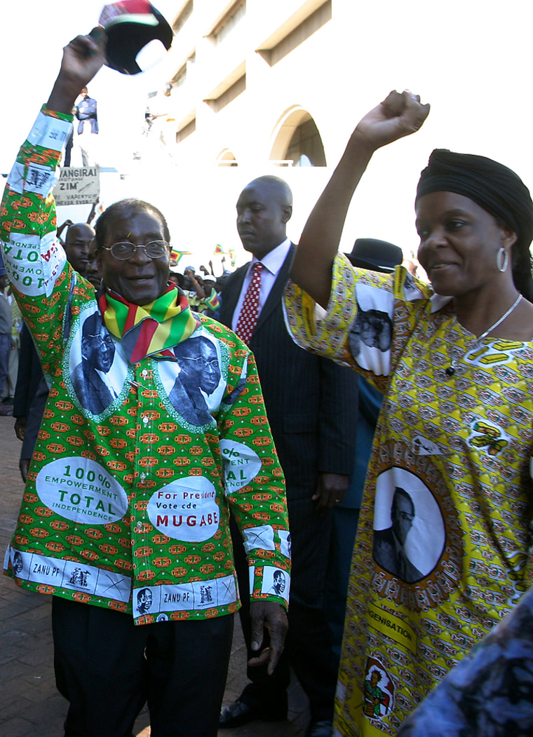 President Robert Mugabe, left, and his wife Grace greet party supporters Sundayat the launchof his runoff election campaign in Harare.