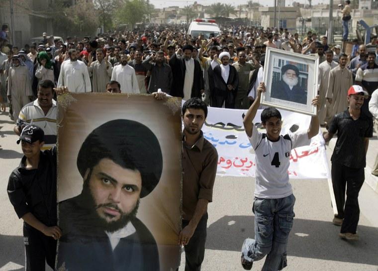 image: Iraqis display banners of Shiite radical cleric Moqtada al-Sadr