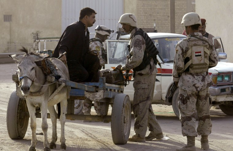 Image: Iraqi soldiers search a street vendor