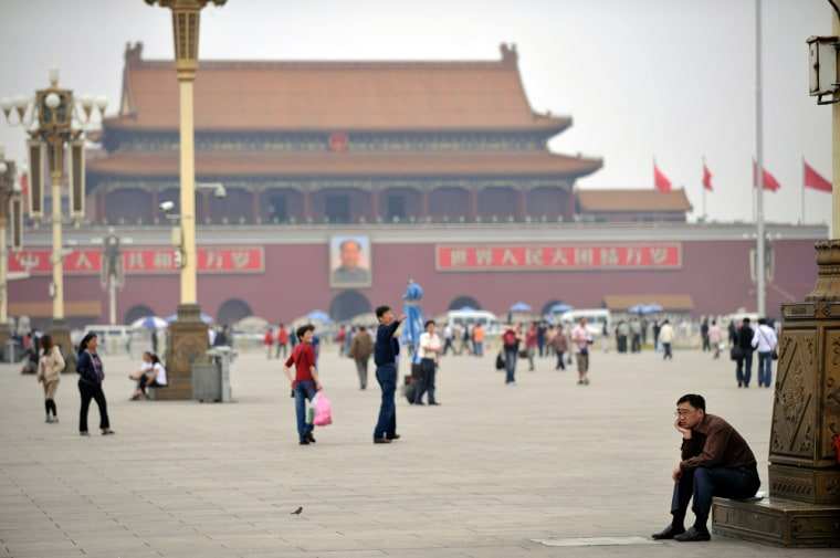Image: A visitor takes a rest on Tiananmen Square