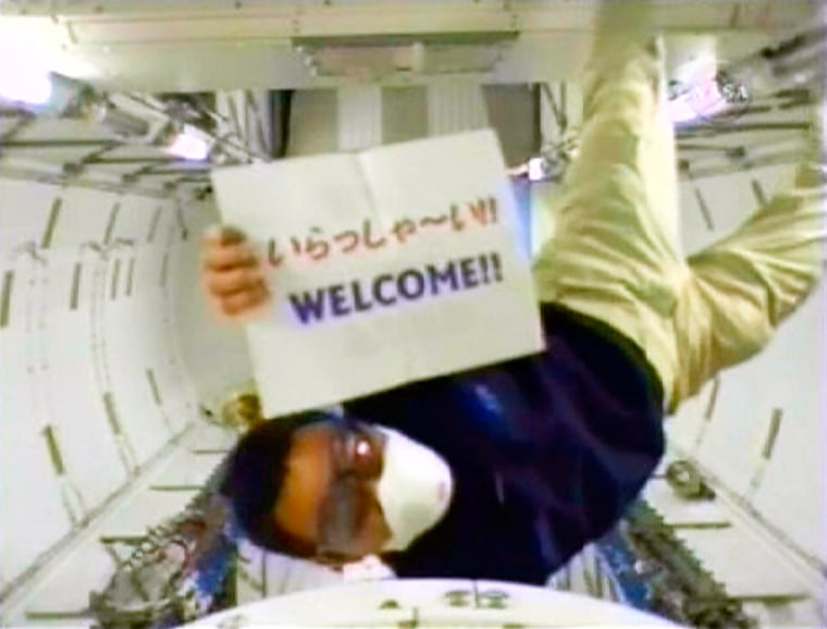 Japan Aerospace Exploration Agency astronaut Akihiko Hoshide holds a welcome sign written in both Japanese and English as he is the first to enter the new Kibo laboratory of the International Space Station