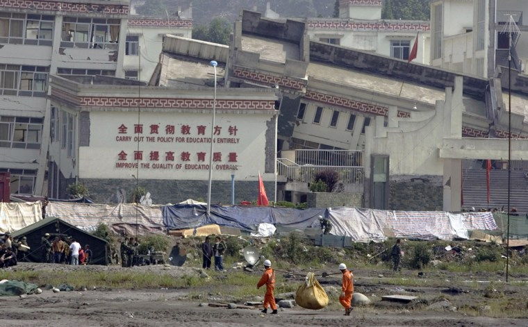 Rescue workers carry supplies past the main building of a school devastated by the May earthquake in Yingxiu insouthwestern China's Sichuan province. The Chinese government said it would investigate why so many school buildings collapsed in the quake.
