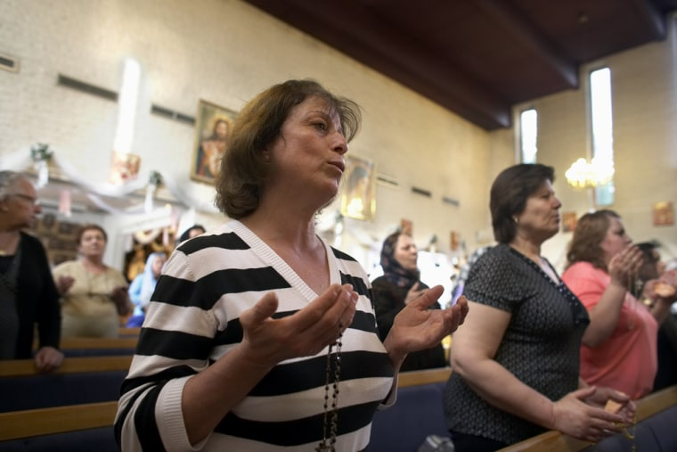 Nagiba Daud, front, prays atJohannes Church in Sodertalje, Sweden. The 52-year-old devout Christian fled Baghdad with her two sons after their family received death threats and their house was burned down.