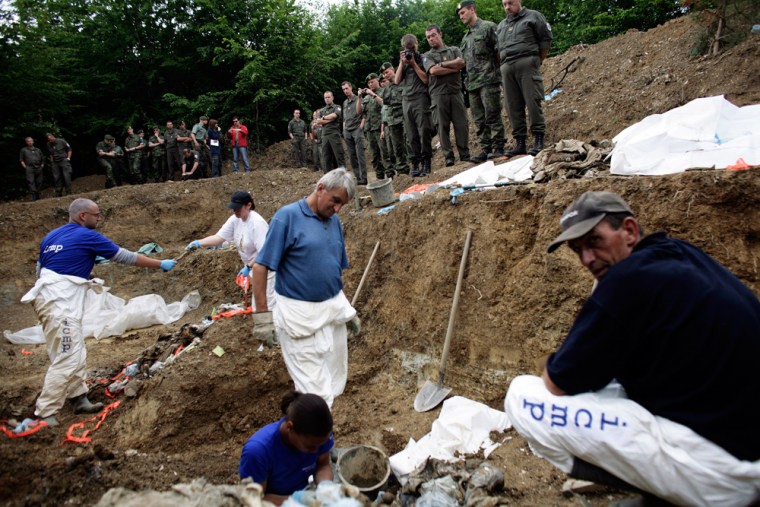Image: Forensics experts at the mass grave