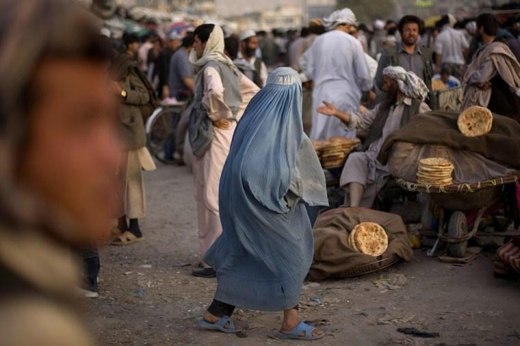 Image: A walks through a market in Kabul
