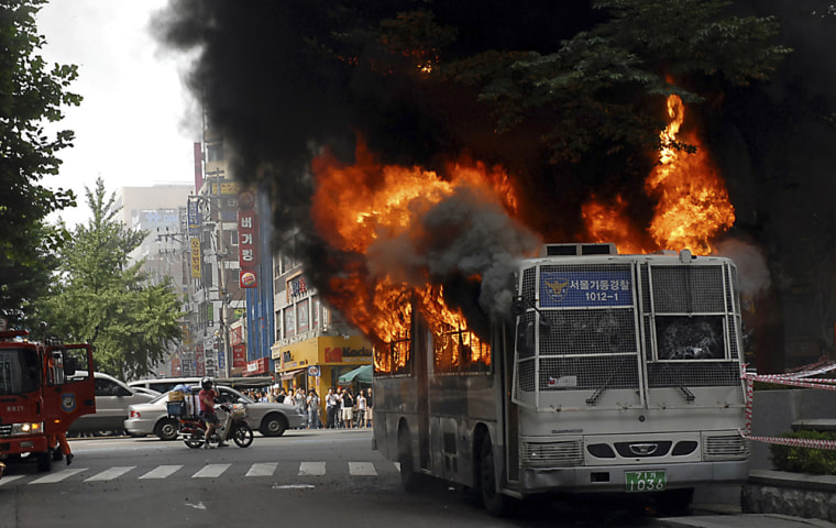 Image: A police bus, which was used to block an anti-U.S. rally against government's policy for beef imports, burns