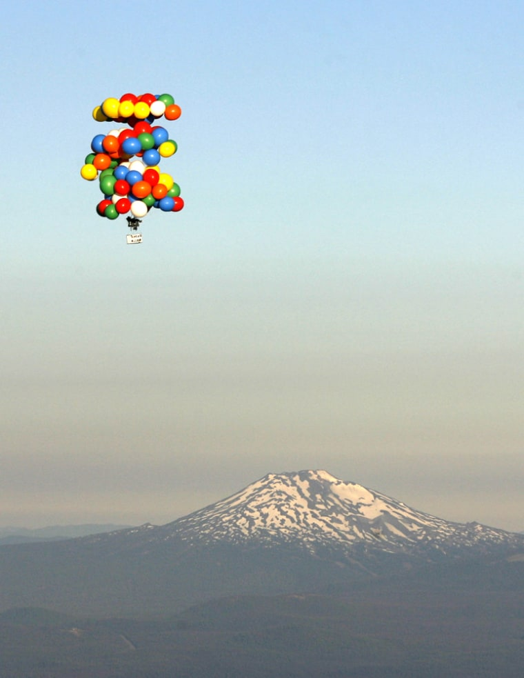 Image: Cluster balloonist Kent Couch, sitting in a lawn chair, ascends past Mount Bachelor