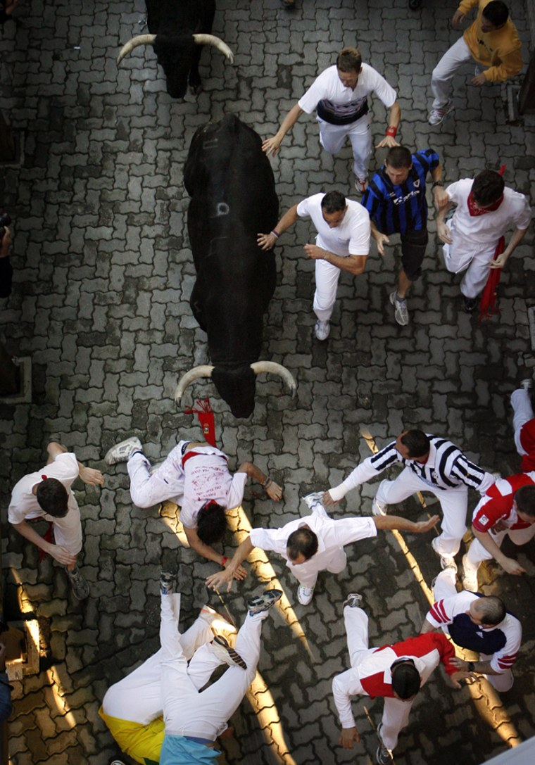 Image: Revelers are chased on the first day of the running of the bulls in Pamplona, Spain