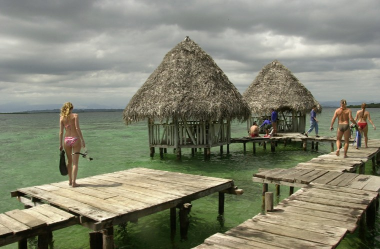 Image: Tourists walk along the docks of the snorkeling area of Coral Key in Bocas del Toro, Panama