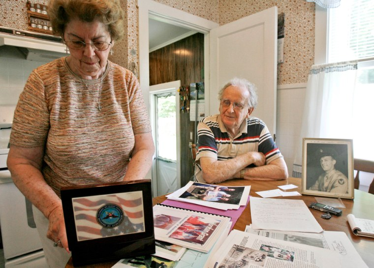 Mary Shostak opens a box containing a dog tag and class ring belonging to Felix Shostak as her husband, Charles, seated, looks on in Proctor, Vt.