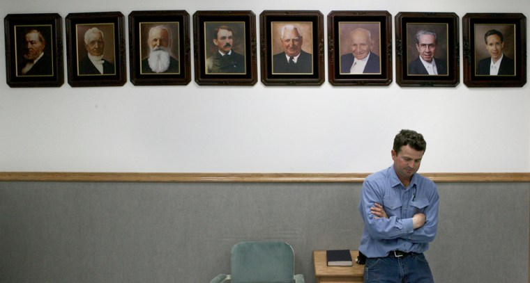 A man leans on a desk in his living room, underneath portraits of FLDS prophets on the Yearning For Zion ranch, the polygamous community in Schleicher County near Eldorado,Texas, on April 12.