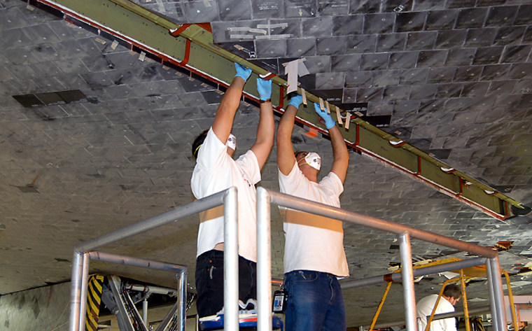 Technicians work on insulation tiles near the shuttle Discovery's landing-gear door at the Orbiter Processing Facility at NASA's Kennedy Space Center.